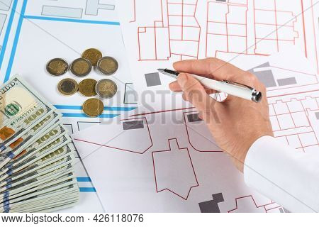 Cartographer With Money Drawing Cadastral Map, Closeup