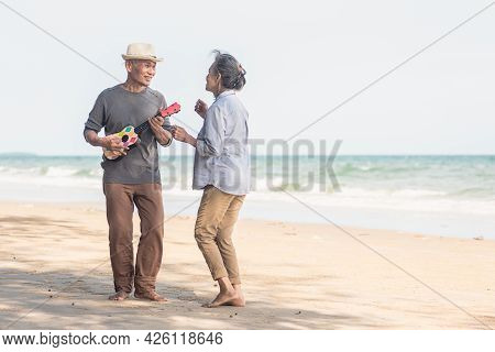 Happy Senior Couple Relaxing Outdoors Singing And Playing Acoustic Guitar At Beach Near Sea Sunny Da