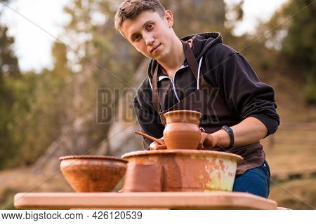 Man Potter Work With Clay Ware. Young Handsome Man Potter On His Workshop.