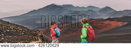 Hawaii Maui hikers couple hiking in mountains landscape banner panorama. Woman and man walking on hike of Haleakala volcano looking at view happy enjoying healthy outdoor lifestyle.