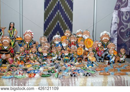 Traditional Ceramic Figurines Of Happy Uzbek Men In National Clothes With Bread In Hands