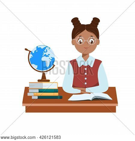 A Cute Black Schoolgirl With Glasses Sits At Her Desk. Books And A Globe Are On The Table. The Book