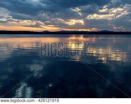 Darkening Sunset Sky Over The Lake With Colorful Clouds, Golden Hour