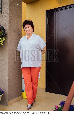 A Elderly Woman In A White Blouse And Orange Trousers Stands On The Doorstep