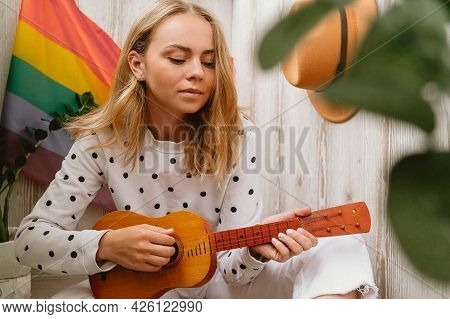 Young Millennial Hippie Woman Sitting On Balcony Play Guitar. Music Lesson And Singer Sitting. Lgbtq