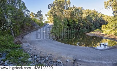 A Road Winding Over And Around A Country Creek In Early Morning Light. Sandy Creek, Mackay, Queensla