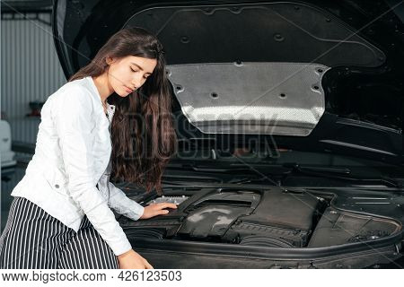 Young Woman Standing In Front Of The Car With Opened Hood In Garage Looking Under Car Hood