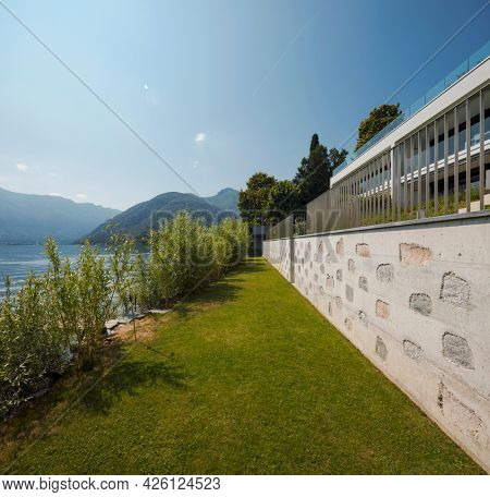 Exterior of a modern house, the garden overlooks the lake. A landscape that gives a feeling of bliss