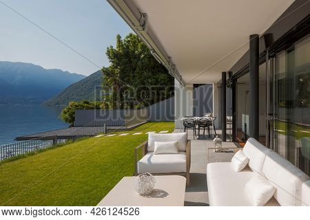 Private terrace overlooking Lake Ceresio in Switzerland. In front of a beautiful green lawn, small table, armchairs and sofa, all white. It's a sunny day and it's midsummer