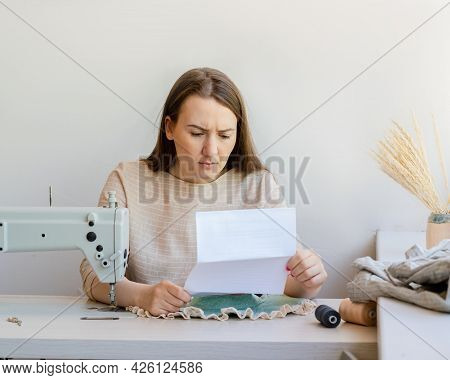 Young Female Owner Of Fashion Atelier Feeling Upset While Reading Tax Bill And Worried About Trouble