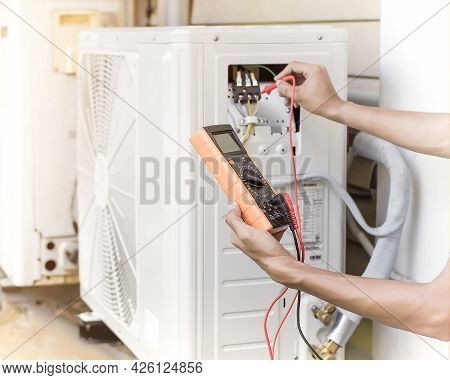 Air Conditioner Repairman Using Electricity Meter To Check Air Conditioner Operation, Maintenance Co