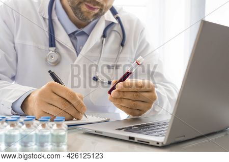 Doctor While Working In His Office. He Is In Charge Of Describing A Blood Sample In A Test Tube. Res
