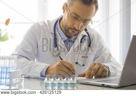 Doctor During Work In The Laboratory. He Sits In Front Of A Laptop Monitor And Records The Results O