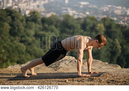 Caucasian Athlete With Muscular Bare Torso Standing In Plank Position On Yoga Mat On Fresh Air. Youn