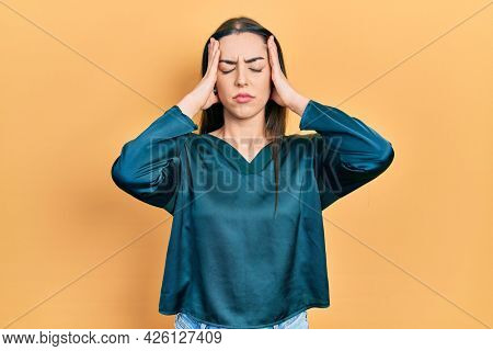 Beautiful woman with blue eyes wearing elegant shirt suffering from headache desperate and stressed because pain and migraine. hands on head.