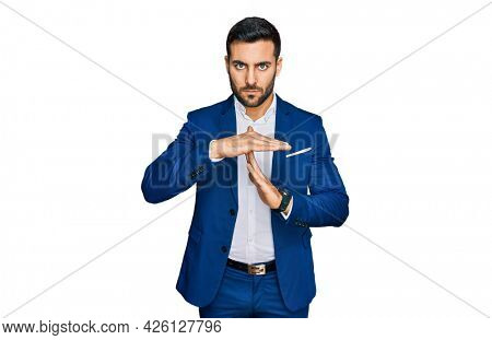 Young hispanic man wearing business jacket doing time out gesture with hands, frustrated and serious face