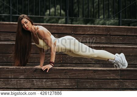 A Young Female Holding A Plank In A Park In The  Summer Day. Portrait Of A Woman With Pumped Up Musc