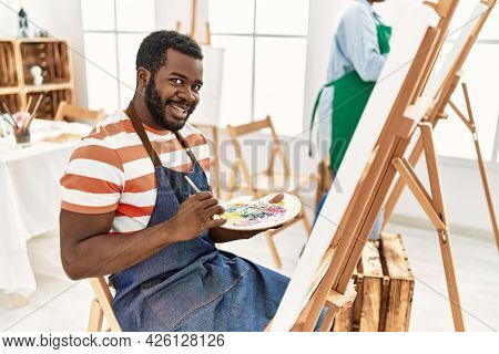 African american painter couple smiling happy painting at art studio.