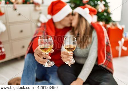 Young couple wearing christmas hat covering with blanket. Sitting on the floor toasting with champagne at home.