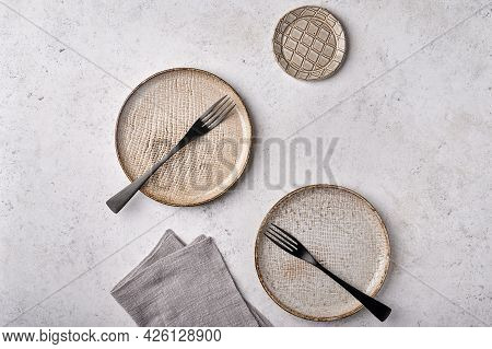 Empty Light Textured Plates With Forks And Napkin Set On Gray Background. Top View, Copy Space