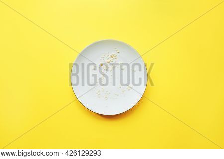 Conceptual Image Of The End Of The Holiday. Empty Round Plate With Crumbs On Yellow Background.