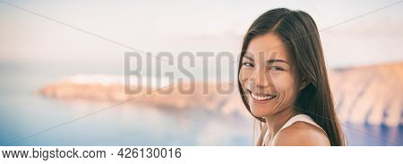 Asian woman young beautiful girl smiling at camera with panoramic view of Oia greek island travel destination. luxury cruise vacation outdoor balcony with view of the mediterranean sea, Greece banner.