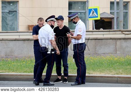 Moscow, Russia - July 2021: Russian Police Officers In Face Masks Are Checking The Documents Of Two