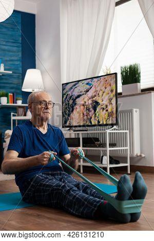 Retirement Senior Man Sitting On Yoga Mat Stretching Legs Muscles Using Resistance Elastic Band Trai