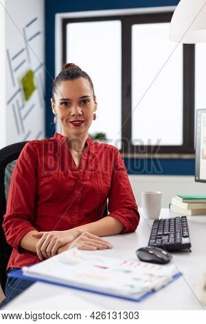 Portrait Of Start Up Enterprise Company Leader Smiling At Camera While Doing Financial Paperwork. Su