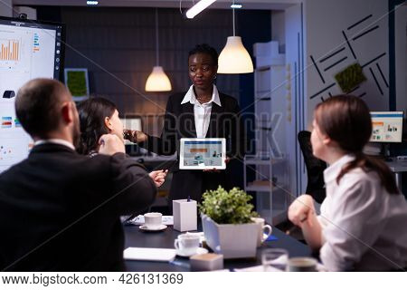 Exhausted Workaholic African American Showing Financial Graphs Using Tablet Overworking In Company O