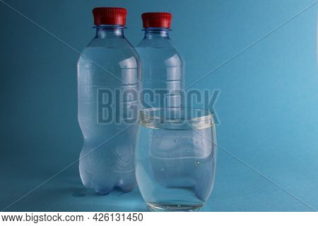 Water In A Glass And Nearby There Are Water Bottles On A Blue Background. Cool Soft Drinks In Summer