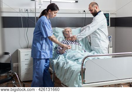 Hospitalized Senior Woman Inhale And Exhale Through Oxygen Mask Laying In Hospital Bed. Medical Nurs