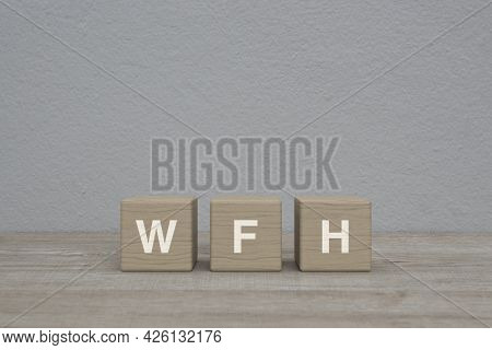 Wfh Letter On Block Cubes On Wooden Table Over White Wall Background, Business Work From Home Concep