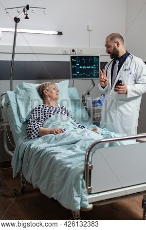 Unwell Senior Woman Patient Laying In Hospital Bed. Listening Doctor Specialist Discussing About Tre