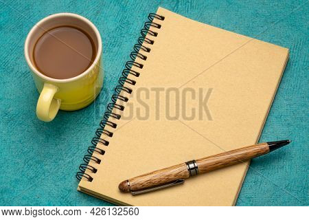 blank spiral art sketchbook with a stylish pen and a cup of coffee, business or journaling concept