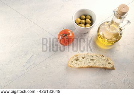 A Slice Of Bread With Olives, Tomato And Olive Oil On White Textured Background. Top View. Flat Lay.