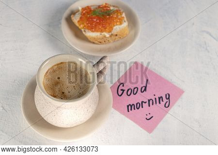 A Cup Of Coffee With A Sandwich With Red Caviar And Next To A Note With The Words Good Morning. Top
