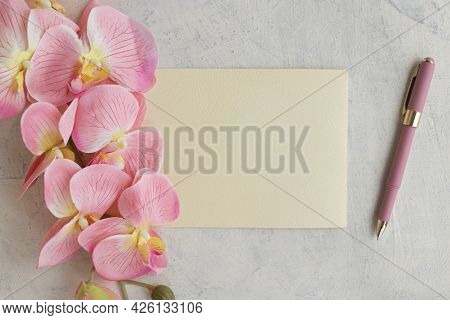 Congratulations Or Holiday Concept. Flat Lay Of Blank Textured Leaf With Pink Pen And Pink Orchid On