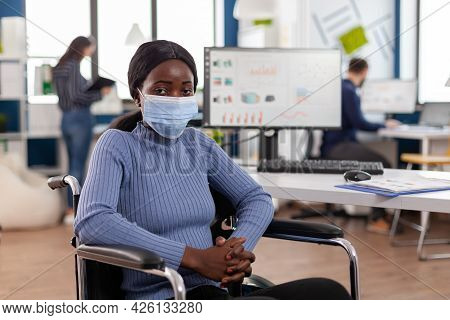 Immobilized Paralized Handicapped African Employee Looking At Camera Wearing Protection Mask During