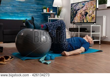 Retirement Senior Man Doing Wellness Warming Legs Up Using Swiss Ball Sitting On Yoga Mat In Living