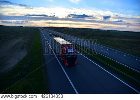 Semi Truck Transporting Sea Container On Highway On Sunset Background. Shipping Containers Delivery,
