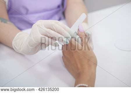 Cropped Shot Of Manicurist Filing Thumb Fingernail Of Female Client