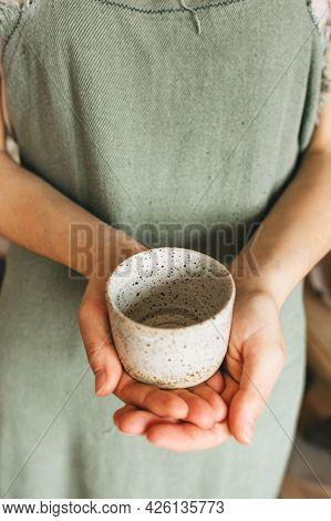 An Artisan Woman Holds A Handmade Ceramic Cup In Her Hands. Small Business