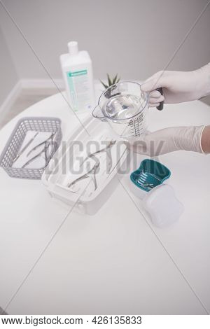 Vertical Cropped Shot Of Professional Manicurist Using Liquid Sterilizer, Cleaning Her Instruments