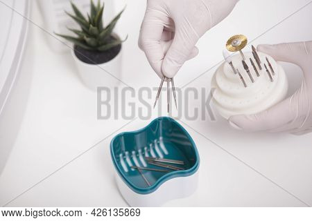 Cropped Close Up Of Manicurist Putting Nail Drill Bits Insto Sterilizer