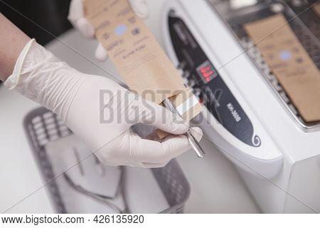 Close Up Of Professional Manicurist Preparing Manicure Tools For Sterilization In Dry Heat Sterilize