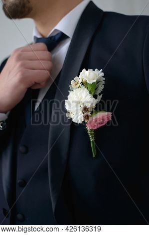 Groom In A Dark Blue Suit With A Boutonniere Adjusts His Tie Looking To The Side In Close-up