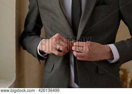 Groom In A Gray Suit With A Tie Fastens A Button On His Suit Close-up