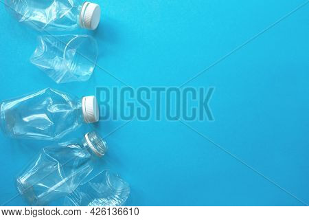 White Plastic Garbage On A Blue Background. The Concept Of Plastic Recycling And Ecology. Plastic Wa