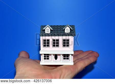 Miniature House In Hand On Blue Background. Home Buying Or Selling. Home For Family. Real Estate Inv